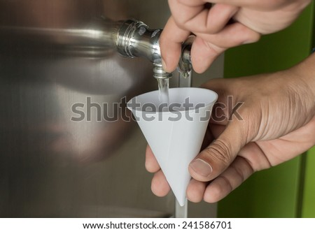 Filling a Paper Cup from a Water Cooler - stock photo