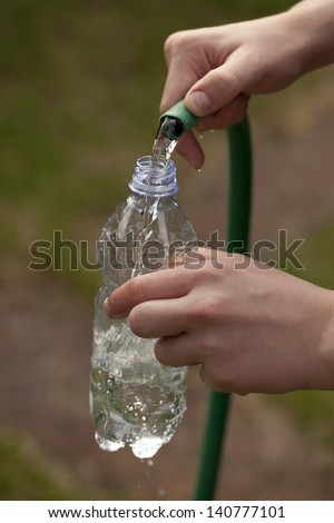 Filling a plastic bottle some water with a hose