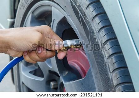 Filling air into a car tire.