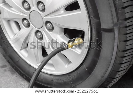 Filling air into a car tire  - stock photo
