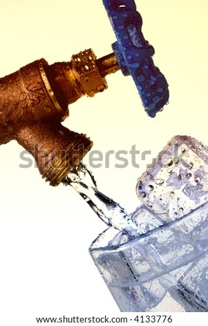 Filling glass of ice cubes with water from a faucet. - stock photo