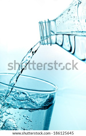 filling glass of water from a bottle of mineral water