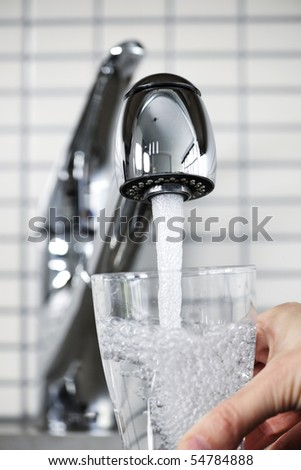 Filling glass of water from stainless steel kitchen faucet - stock photo