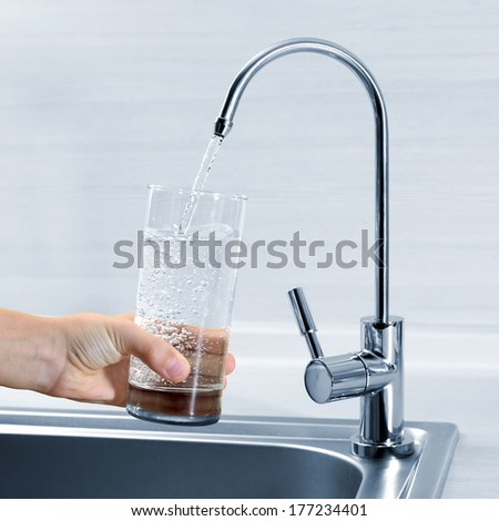 Filling glass of water in hand from kitchen faucet - stock photo