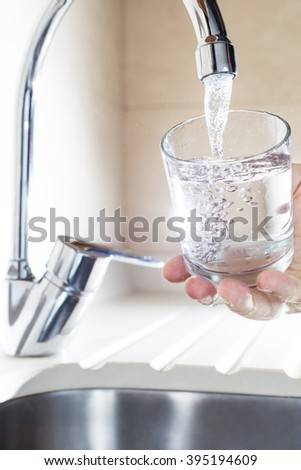 Filling glass of water in hand from kitchen faucet. Concept of safe water and healthy life - stock photo