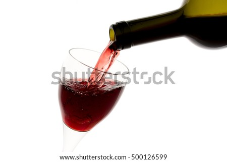 Filling glass with red wine from green bottle