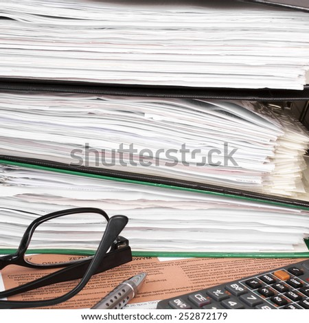 Filling in polish individual income tax form PIT with calculator and pen - stock photo