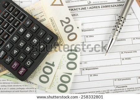 Filling in polish individual income tax form PIT with money and pen - stock photo