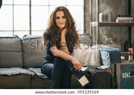 Filling inspired for adventure! Smiling elegant woman with passport, ticket and luggage sitting on sofa in loft apartment while waiting for departure. Happy holiday and travel concept