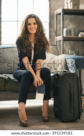 Filling inspired for adventure! Smiling elegant woman with passport, ticket and luggage sitting on sofa in loft apartment while waiting for departure. Happy holiday and travel concept - stock photo