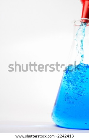 Filling large beaker with blue liquid - stock photo