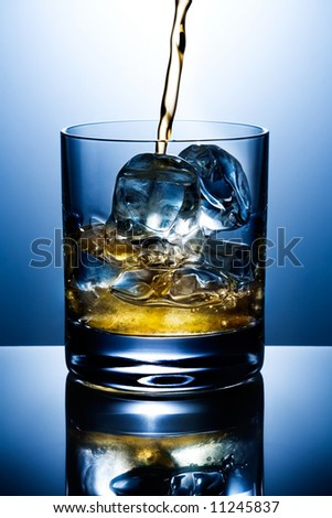 Filling of a glass of whisky with ice - stock photo