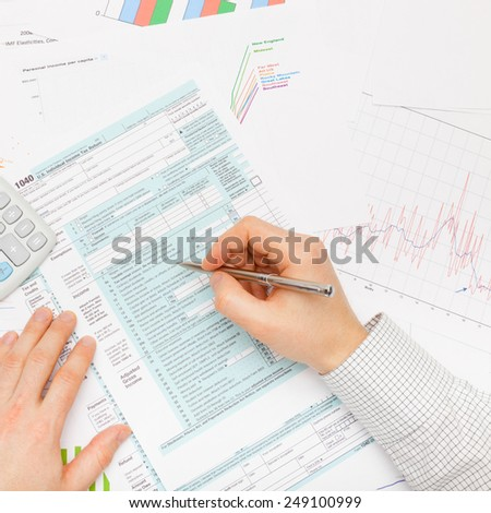 Filling out 1040 US Tax Form - studio shot - stock photo