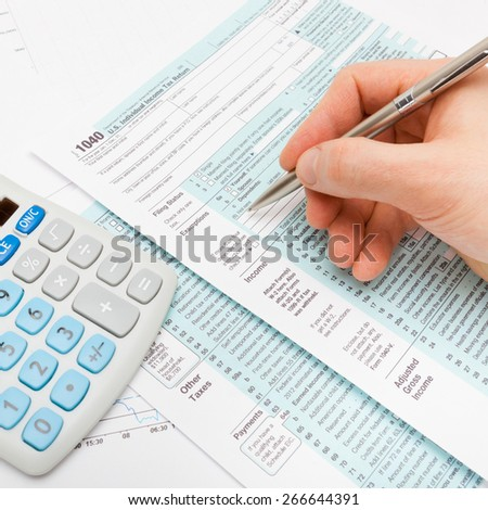 Filling out US 1040 Tax Form - studio shot - stock photo