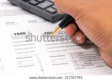 Filling out 2014 US Tax Form with ballpoint and calculator - stock photo