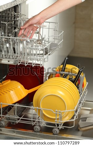 Filling the dishwasher in a modern kitchen