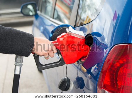 Filling the tank of a car in a gas station. Woman fills the tank of her beautiful blue efficient car at a pump in a gas station in Toronto - stock photo
