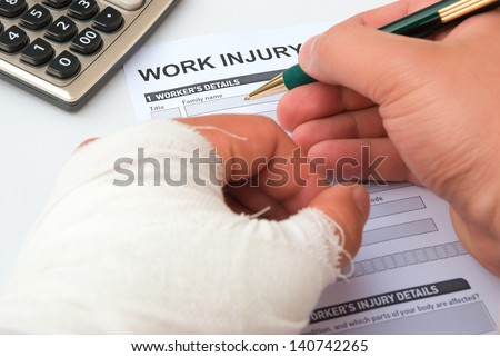 filling up a work injury claim form with a wrapped hand, calculator in corner, medical and insurance concept - stock photo