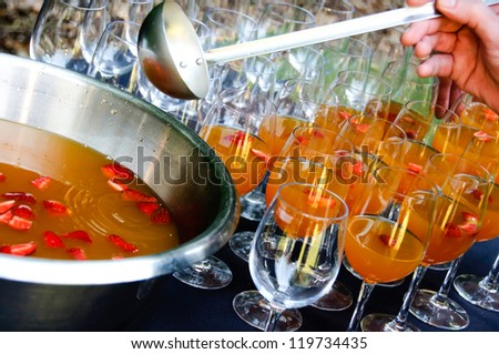 Filling up punch drink glasses - stock photo