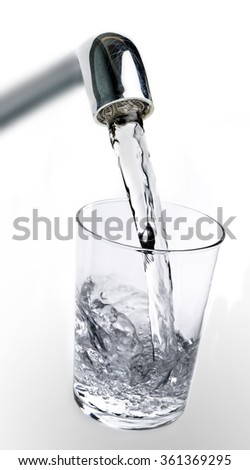 Filling water from the tap into a glass on white