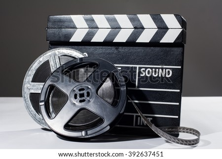 Film camera chalkboard and roll on white table. Accessories for shooting and film screenings - stock photo