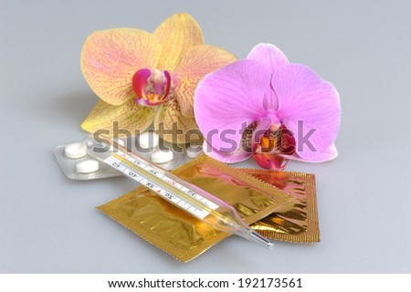 Film-coated tablets, condoms and thermometer with two orchid flowers on gray - stock photo