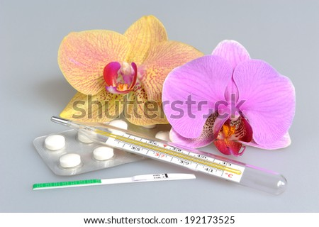 Film-coated tablets, mercury thermometer and ovulation test with two orchid flowers on gray - stock photo