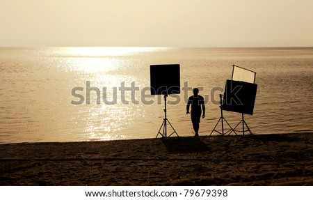 film crew setting up scene on a beach - stock photo