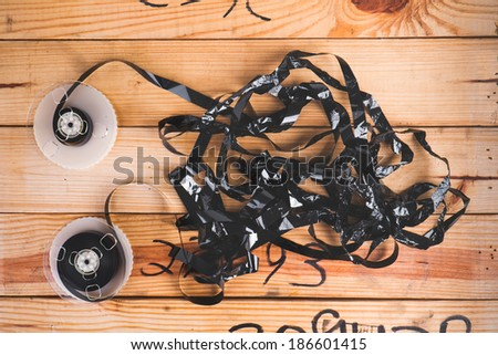 film from vdo cassette tape ruined on wooden table - stock photo