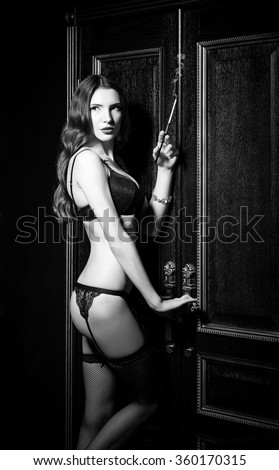 Film noir style: sexy gorgeous young woman in underwear standing at the door and smoking cigarette
