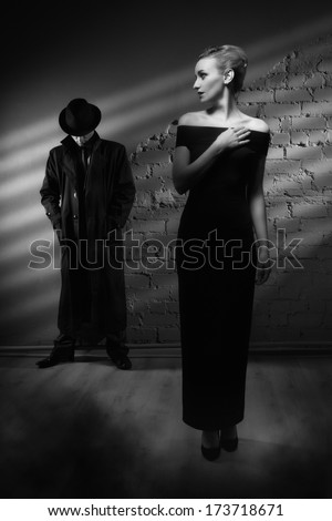 Film noir. Woman in a long black dress and a man in a raincoat and hat - stock photo