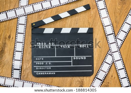 Film slate and film stripes on a wooden background - stock photo