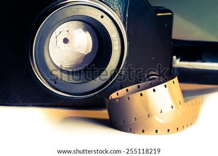 Film strips closeup with vintage movie cinema camera with lens on background - stock photo