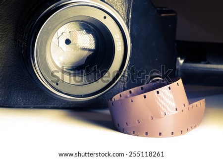 Film strips closeup with vintage movie cinema camera with lens on background