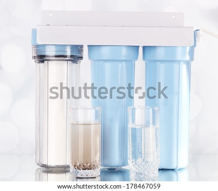 Filter system for water treatment with glasses of clean and dirty water on bright background - stock photo
