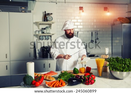 Filtered image, handsome chef in uniform cleaning his knife before began meal preparation - stock photo