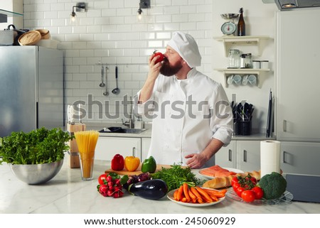 Filtered image, male chef  in uniform smell aroma of fresh tomato standing on big professional kitchen - stock photo