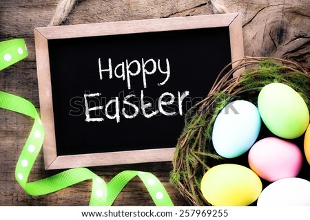 Filtered image of Vintage blackboard on a wooden background with colourful Easter eggs - stock photo