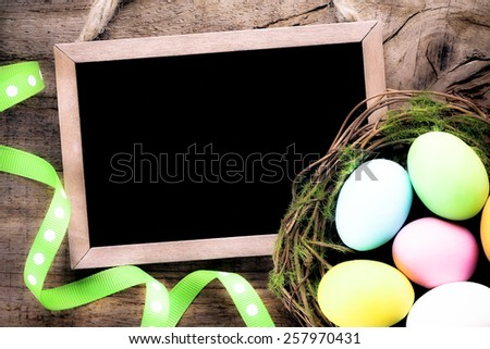 Filtered image of Vintage blackboard on a wooden background with colourful Easter eggs with copy space for your text - stock photo