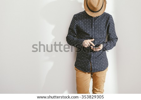 filtered photo of a young stylish man holding a smartphone - stock photo