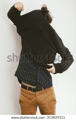 filtered photo of a young stylish man trying to dress a sweater - stock photo