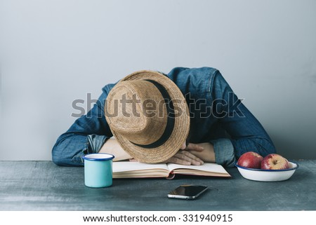 filtered photo of a young tired hipster man having a nap on the desk - stock photo