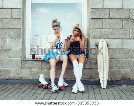 filtered photo of two friends using their smart phones outdoors lifestyle - stock photo
