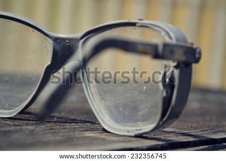 Filtered picture of a vintage safety glasses on a wooden table - stock photo