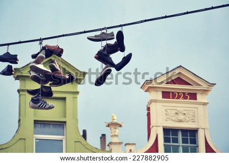 Filtered picture of shoes hanging from a power line in Ghent, Belgium - stock photo