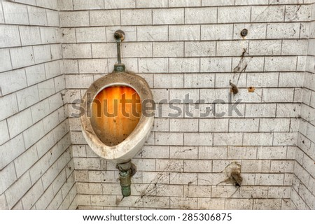 Filthy urinal in the toilet of an abandoned prison. A cleaning challenge. - stock photo