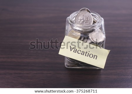 Finacial concept. Money in the glass on wooden table with Vacation word and copy space area.