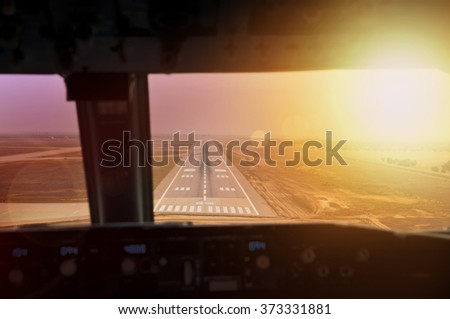 Final approach during sunset. View from flight deck of a modern airliner plane - stock photo