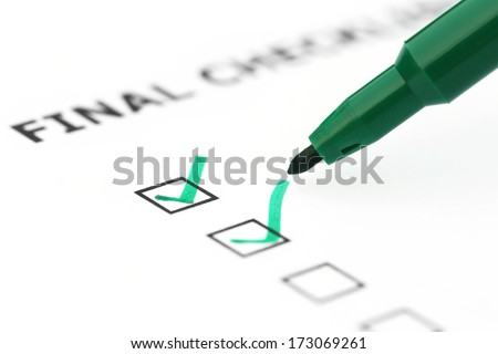 Final Check list with green pen over white paper - stock photo