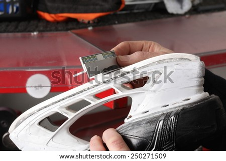 Final control of the sharpened blade of a hockey skate - stock photo